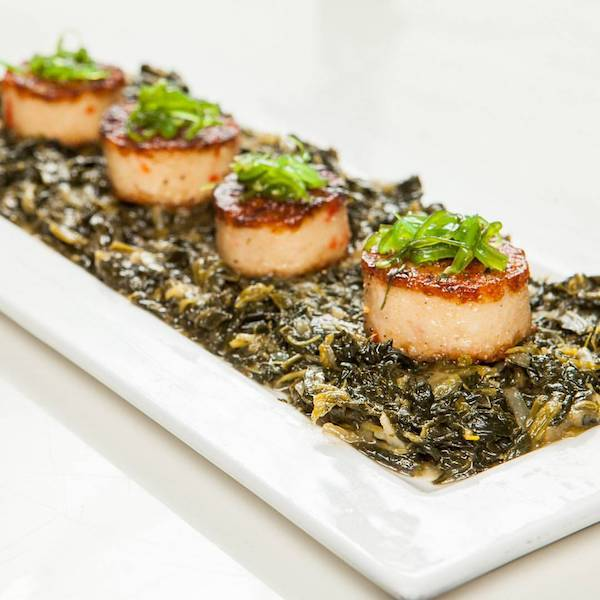 Coquilles St Jacques - from Delice & Sarrasin. Vegan grilled scallops (made with potato starch and tapioca) on top of a sauteed garlic onion spinach and seaweed. Photo: Delice & Sarrasin/Facebook